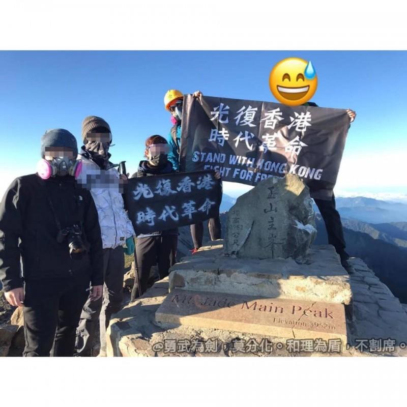 有人帶著防毒面具、頭盔,並在玉山主峰頂上展示出黑旗。(圖擷取自TG)
