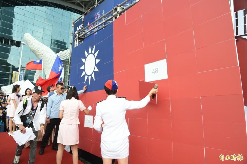 高雄市政府今天在高雄展覽館舉辦國慶升旗典禮,韓國瑜致詞過程中,大幅國旗拼圖看板突然掉落,一旁工作人員立即上前將國旗拼圖扶正掛回去,巨幅國旗險些打到韓國瑜本人。(記者張忠義攝)