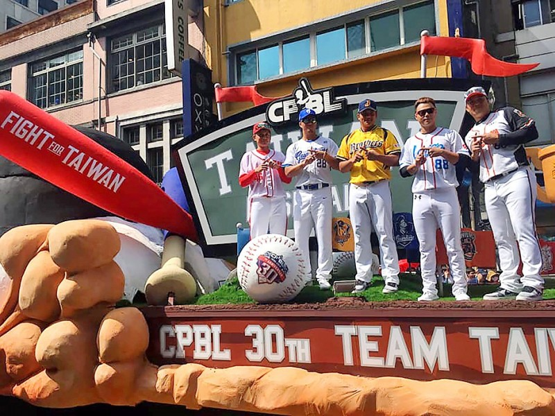"""Chinese Professional Baseball League (CPBL) players, from left, Wei Chuan Dragons Liu Ji-hong, Fubon Guardians Kao Kuo-Hui, Brothers Baseball Club Huang En-tzu, Lamigo Monkey Lan Yin-lun and Uni-President Lions'Kao Kuo-ching make """"double ten"""" signs with their hands as they ride the league's float during yesterday's Parade of Taiwanese Heroes in Taipei. Photo: CNA"""