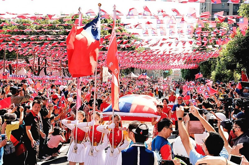 """People take pictures of a parade led by honor guards holding the ROC national flag at a flag-festooned parade through the streets of Taoyuan yesterday. The parade was privately sponsored by Chang Lao-wang, the owner of a noodle restaurant nicknamed """"House of National Flags"""" in Taoyuan's Jhongli District. Photo: CNA"""