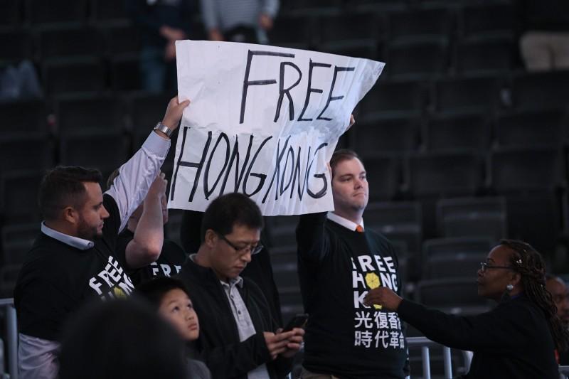 球迷身穿挺港T恤,手舉挺港標語。(美聯社)