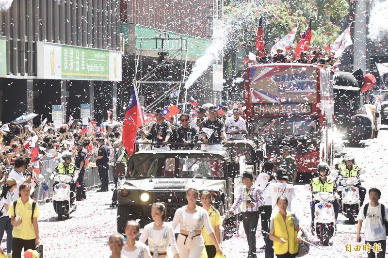 12強台灣棒球代表隊進入館前路,兩旁噴出紙花,民眾揮舞國旗歡迎車隊。(記者陳志曲攝)