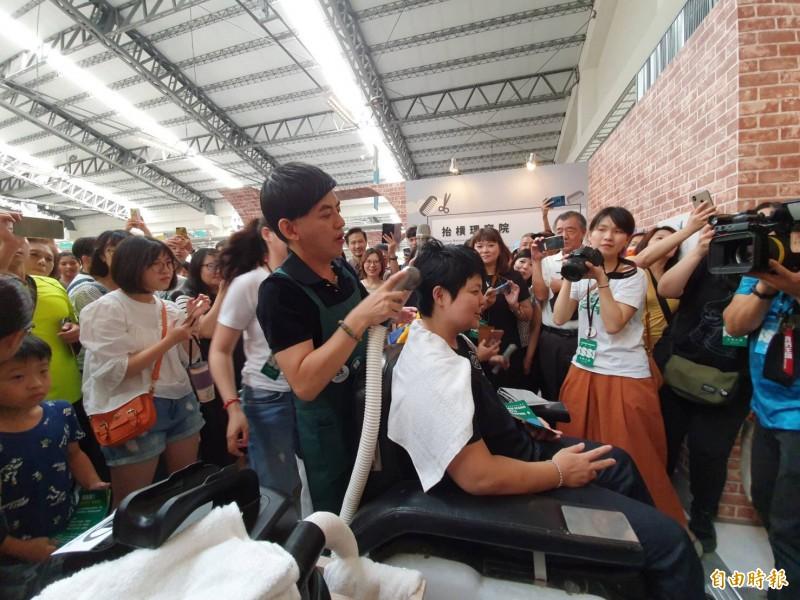 黃子佼現場操作不滴水洗頭機幫民眾洗頭,吸引民眾圍觀。(記者羅欣貞攝)