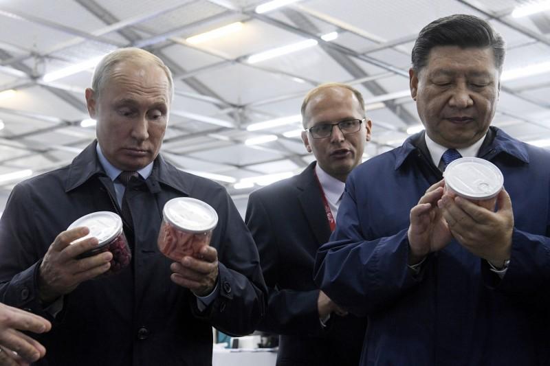 俄羅斯總統普廷去年9月11日與習近平逛俄國商場,查看許多俄國商品,普廷當場掏腰包買蜂蜜送習。(歐新社)