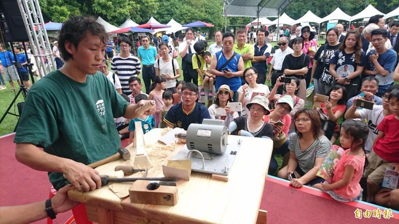 日本匠師現場示範木芥子製作與彩繪,讓民眾近距離欣賞職人精彩的現場實演。(記者楊金城攝)