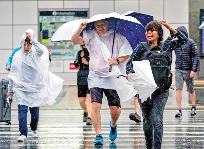 首都東京的行人,在颱風風雨中穿越街頭。日本政府共對超過七百萬人發出避難指示或避難勸告。(歐新社)