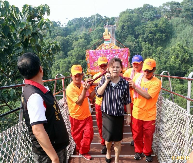 南投市長宋懷琳(女)與信眾一起抬神轎過天空之橋祈福。(記者謝介裕攝)