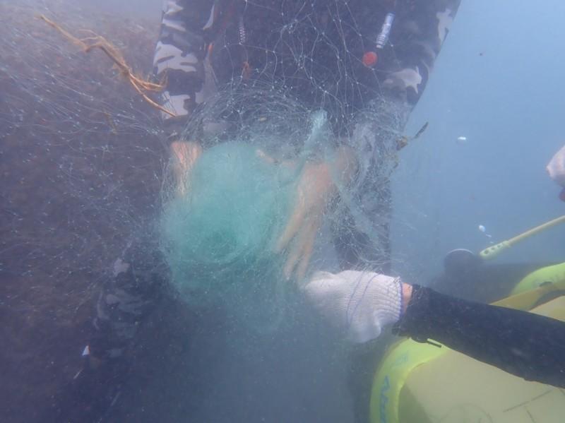 水利署聘請專業潛水者,把廢棄漁網剪掉纏住的部份,再把漁網搓成圓球狀,準備裝進袋子。(水利署提供)
