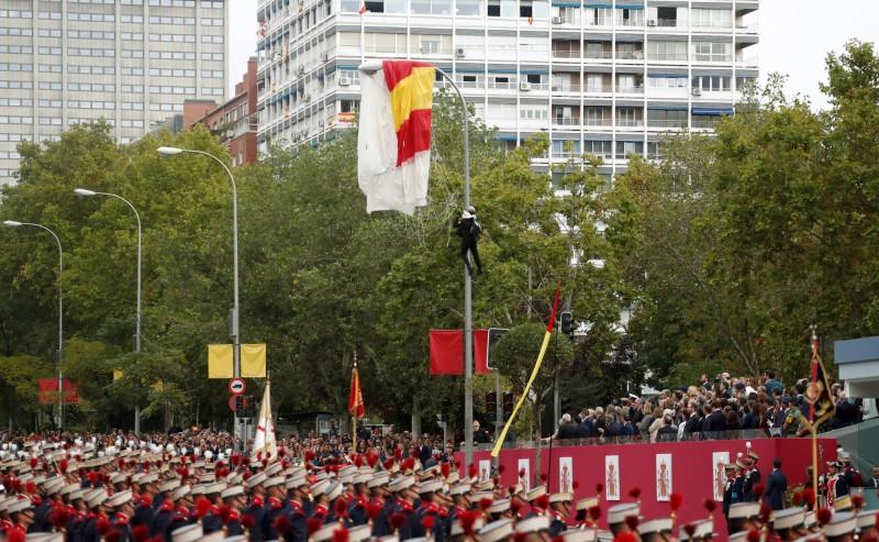 西班牙國慶閱兵,披著國旗的跳傘員在眾目睽睽下掛在路燈上。(路透)