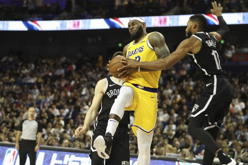 NBA中國熱身賽10日在上海開打,洛杉磯湖人隊「小皇帝」詹姆士(中)正帶球進攻,遭遇布魯克林籃網隊防線強力阻擋。雖然中國有網友發起抵制NBA,這場比賽仍然座無虛席。(美聯社)