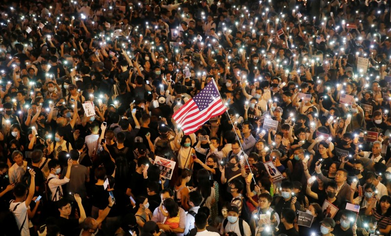 參與集會人士揮舞美國國旗。(路透)