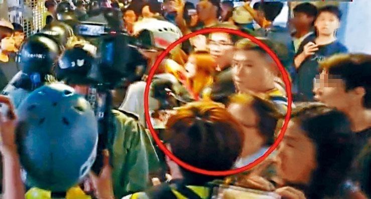 香港13日抗爭,18區同步展開,警民激烈對峙中,一名警察疑遭示威者以美工刀割頸濺血。(圖擷取自香港《星島日報》)