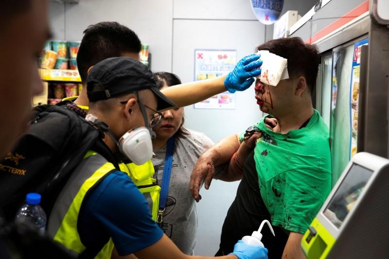 香港13日抗爭中,一名位於將軍澳的店員被示威者暴打成傷濺血,其他示威者幫忙安慰及救助。(路透)