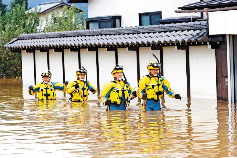 警方14日涉水持續投入救災工作。(路透)