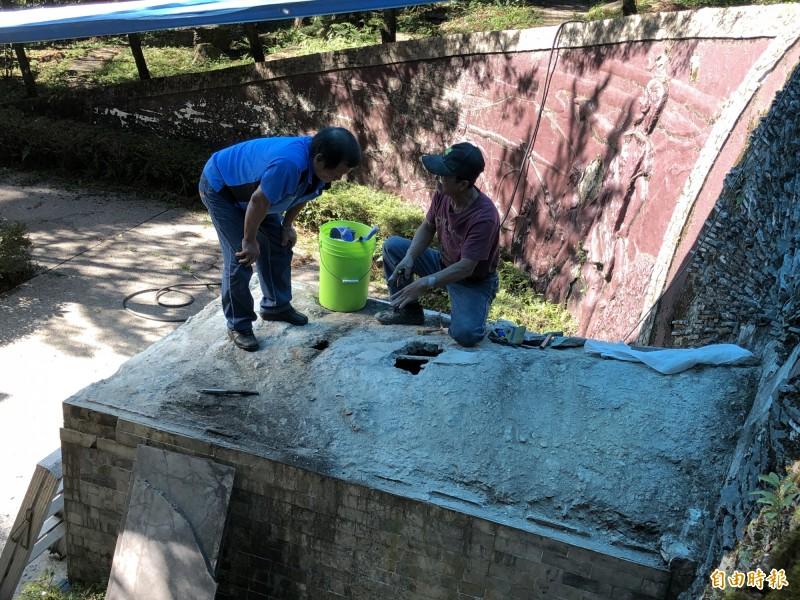 專業修墓師傅先將塌陷的水泥塊挖出小洞,觀察墓穴內部受潮狀況,所幸檜木棺木大致完好。(記者佟振國攝)
