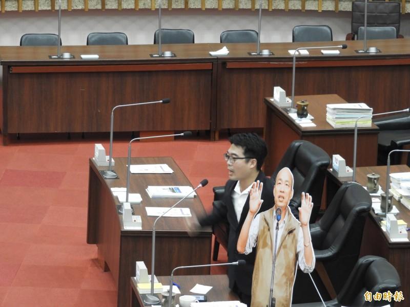 議員邱俊憲拿韓國瑜的人形立牌質詢。(記者葛祐豪攝)