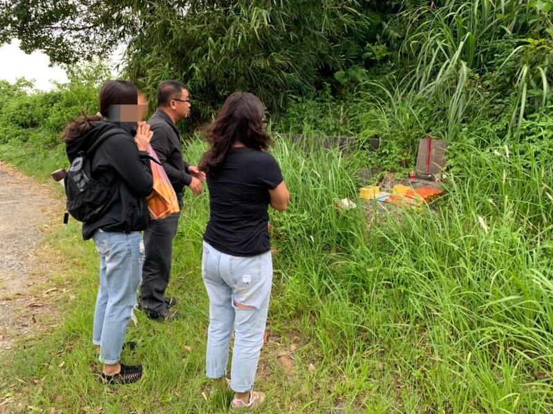 基隆市警一分局三組組長許耀彬,帶著郭婦的家人到汐止第一公墓「無主墓區」找到編號7587的無名墓碑時,郭婦的家人在墳前祭拜。(記者林嘉東翻攝)