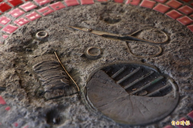 社區營造時將存德中藥房屋內留下的物品鑲嵌在屋前水泥地。(記者林宜樟攝)