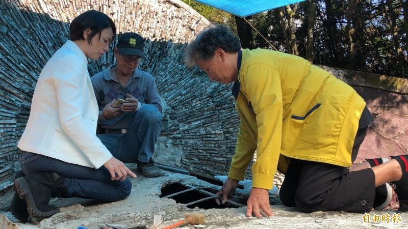 張呈妹(右)與女兒(左)特別爬上墓的上方水泥設施,了解塌陷漏水情形。(記者佟振國攝)