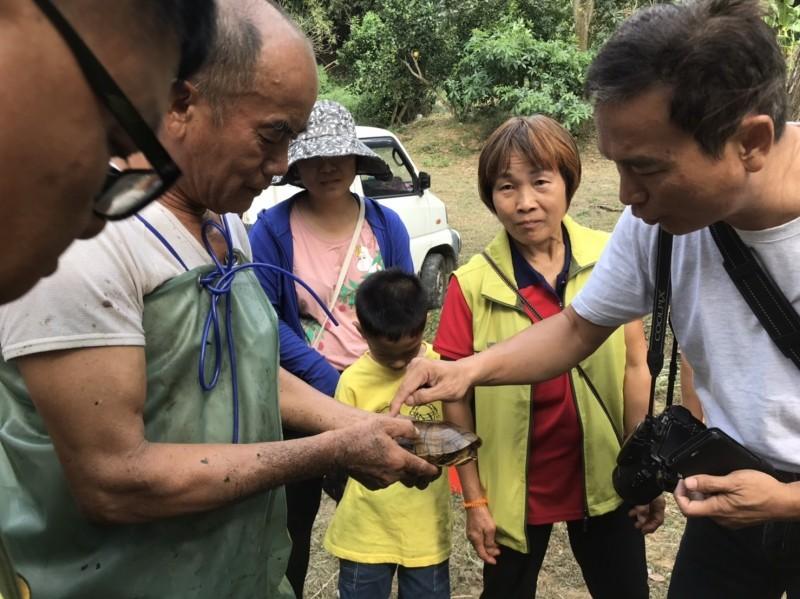 生態解說員拿著捕撈上岸的烏龜,向學童與民眾介紹生態物種。(記者鄭名翔翻攝)