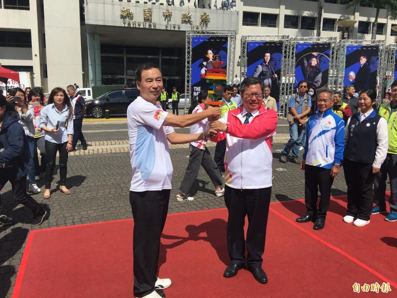 桃園市長鄭文燦將聖火交給桃園區長陳玉明,也展開十三區聖火傳遞行程。(記者謝武雄攝)