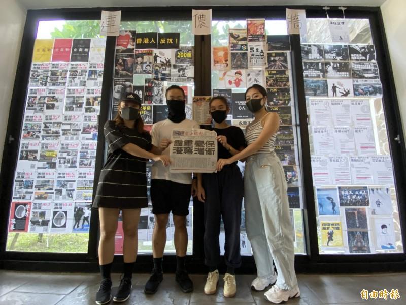 香港劇團帶來恆春半島首面連儂牆,並持《自由時報》撐港廣告合照。(記者蔡宗憲攝)