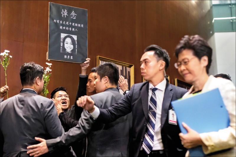 香港特首林鄭月娥17日在立法會接受議員質詢,但時間僅1.5小時,只有3名建制派議員獲得提問機會。人數居劣勢的泛民主派議員只能以呼喊口號和舉標語等方式表達抗議。圖為民主派政黨「新民主同盟」議員范國威,高舉照片悼念9日被發現浮屍海上的15歲少女陳彥霖。林鄭(右)則在保安人牆護送下離開。(彭博)