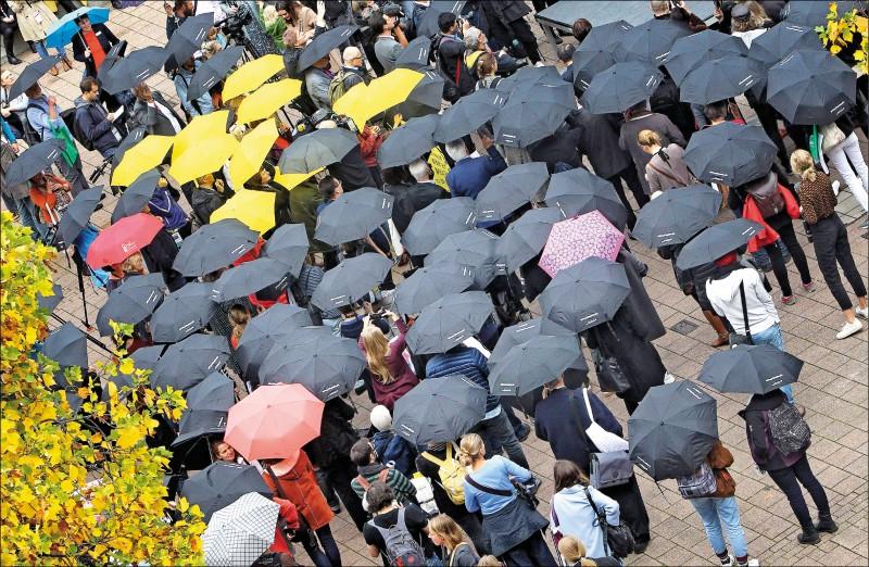 「德國出版業及圖書銷售協會」呼籲全球文學界展現團結,在今年法蘭克福書展以撐雨傘的方式,表達對香港「反送中」運動的支持,做為表達自由和出版與新聞自由的表率。圖為參加該全球最大書展的書迷十七日撐傘響應號召。(法新社)