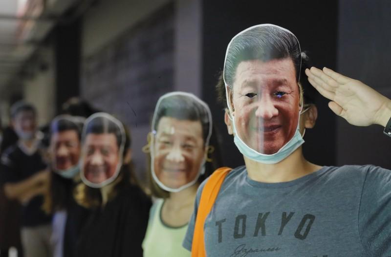 香港反送中示威者今(18日)晚在多區港鐵站一齊戴上面具、手牽手抗議港府日前實施的《禁蒙面法》。(美聯社)