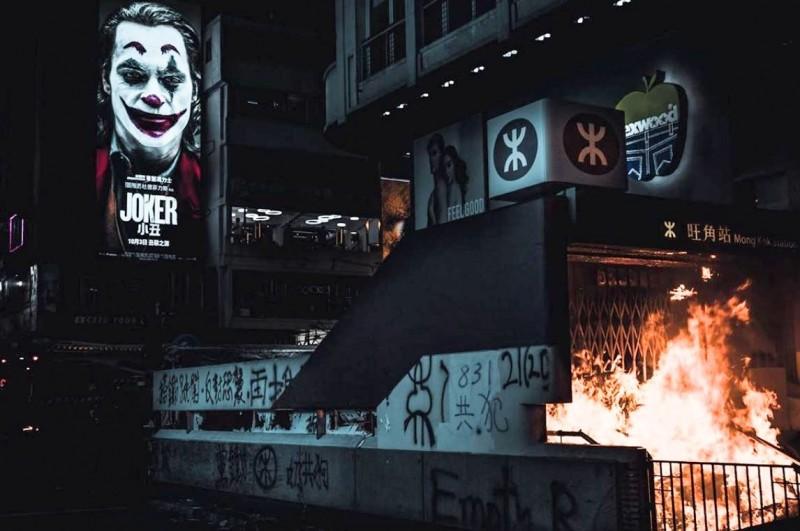 巨幅《小丑》海報凝視著燃燒的港鐵出入口,這張照片在社群媒體上造成轟動。(由Instagram@_fungcw提供)