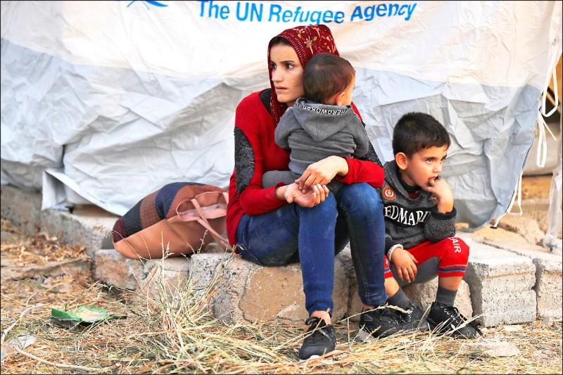 土耳其入侵敘利亞北部的庫德族根據地後,引發逃難潮。圖為十七日正在伊拉克摩蘇爾北部一處難民營等待發放補給品的敘國母子。(美聯社)
