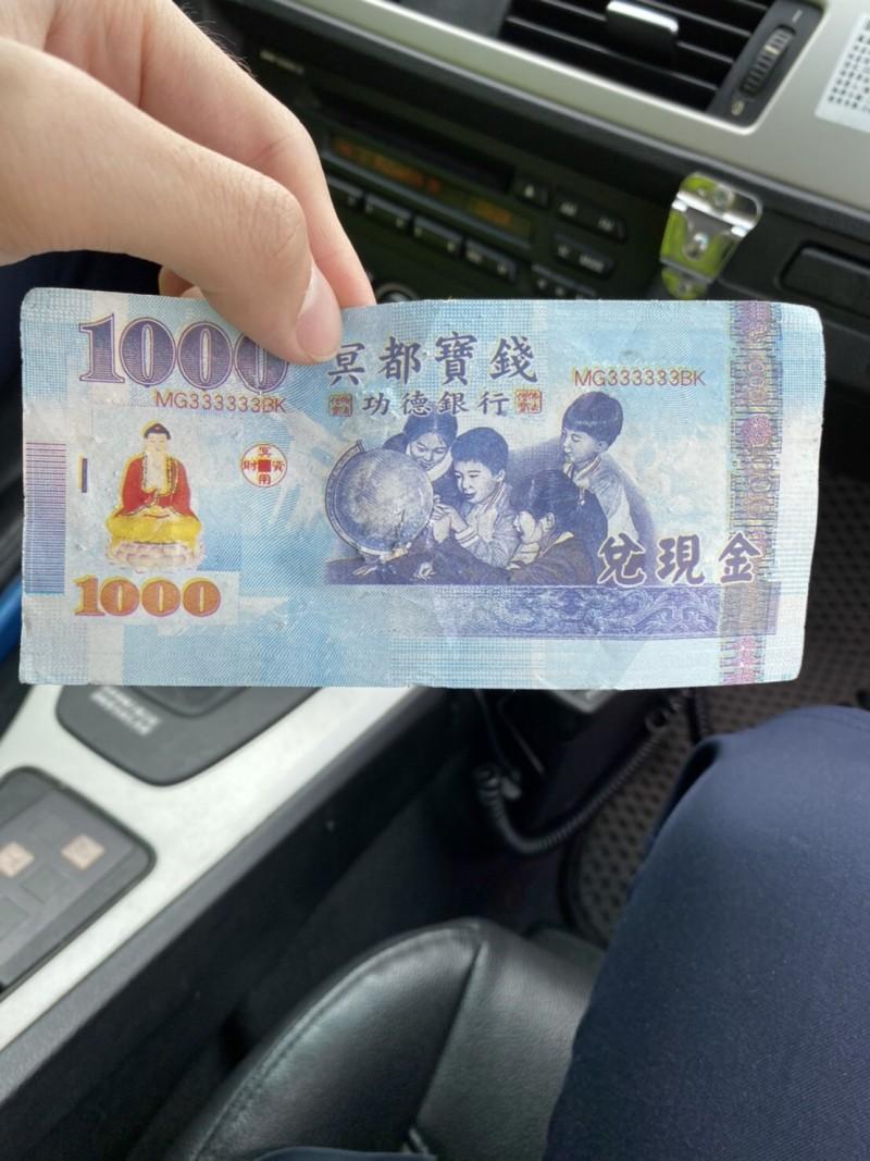 國道警察龍潭分隊巡邏員警到場查看後發現,散落物是「假的」、且面額千元的紙鈔(冥鈔)。(記者李容萍翻攝)