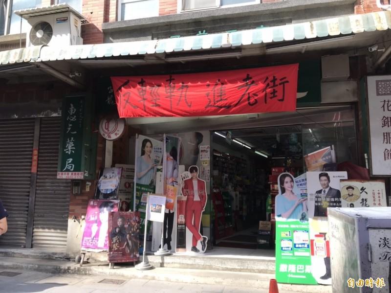 淡水老街數間店家掛起「反輕軌進老街」布條。(記者陳心瑜攝)