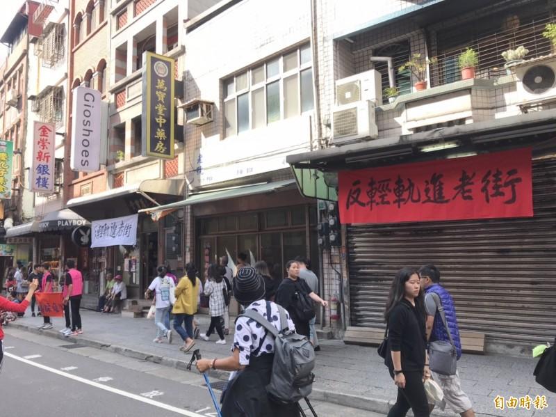 淡水老街數間店家昨天掛起「反輕軌進老街」布條。(記者陳心瑜攝)