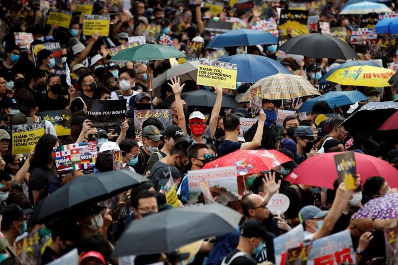 九龍大遊行如期登場,大批民眾撐傘上街。(路透)