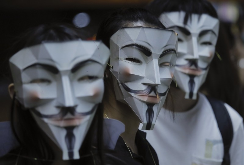 示威者戴上自製的V怪客面具。(美聯社)