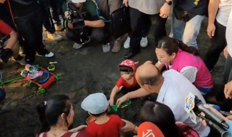 韓國瑜要幫小朋友挖沙,不料小女童不領情,當眾大喊「不要」,並伸手奪回被韓國瑜「借用」的綠色耙子。(圖擷取自臉書_土包子志工團)