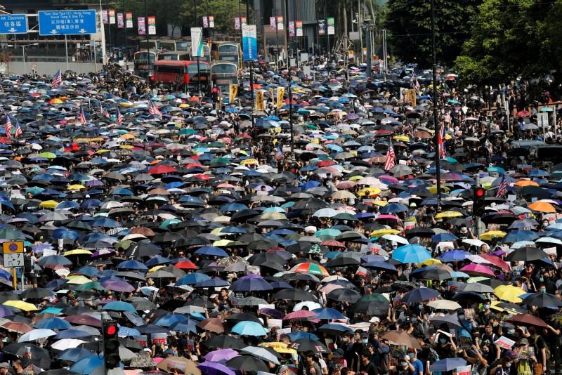九龍大遊行如期登場,大批民眾撐傘上街,除了五大訴求口號外,還有人手持港英旗、美國國旗,甚至我國國旗上街。(路透)