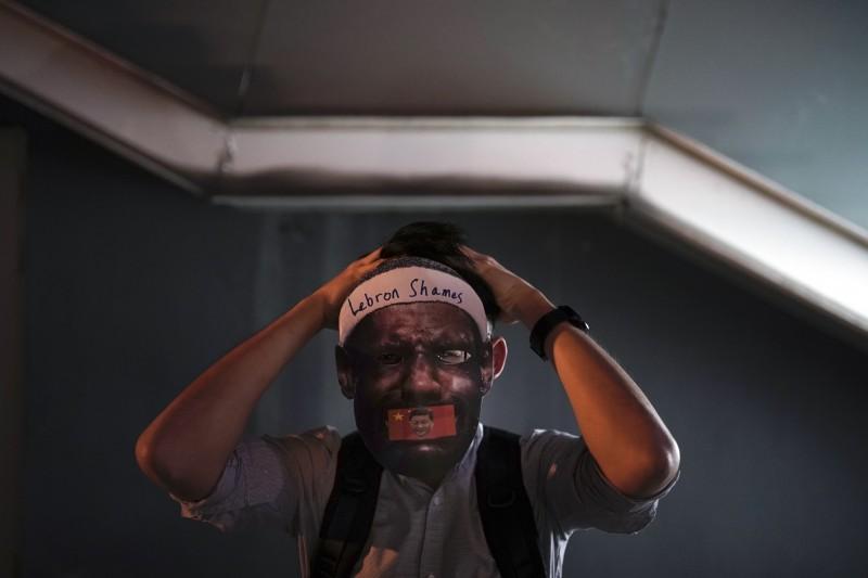 示威者戴上NBA球星詹姆斯面具,諷刺詹姆斯為中國市場不敢支持得罪中共的言論。(美聯社)