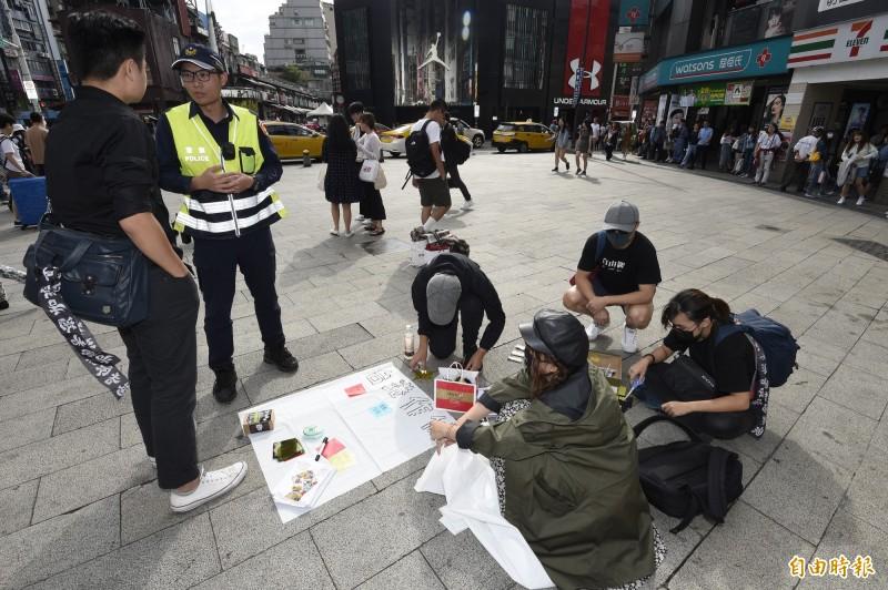 在台港人團體「邊城青年」20日下午在台北市西門町進行千人口罩照募集計劃,或許事件較為敏感,警方也派員到場關切。(記者叢昌瑾攝)