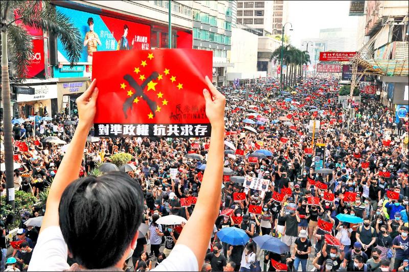 香港民眾二十日在九龍地區遊行,高舉「對準政權,抗共求存」布條。(美聯社)