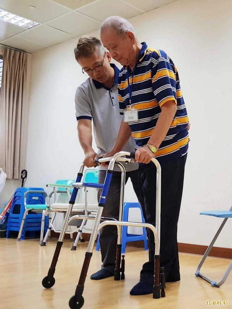 王玄宇(左)協助長輩復健。(記者黃旭磊攝)