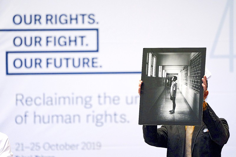 Former death-row inmate Hsu Tzu-chiang holds up a picture at the opening ceremony of the 40th International Federation for Human Rights congress in Taipei yesterday.  Photo: CNA