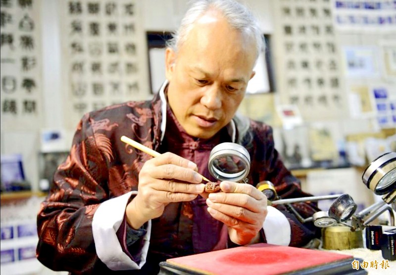 Miniature sculptor Chen Forng-shean demonstrates his craft at his workshop in New Taipei City on Saturday.   Photo: Weng Yu-huang, Taipei Times