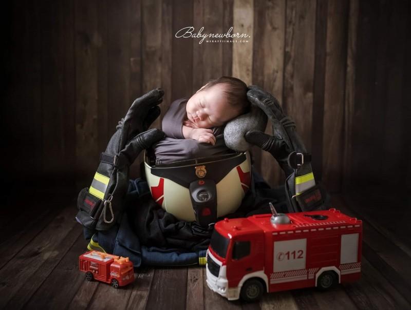男嬰睡在爸爸的消防帽上方,感覺睡得很安穩。(梁琇媚提供)