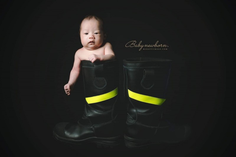 小男嬰坐在爸爸的雨靴中模樣可愛。(梁琇媚提供)