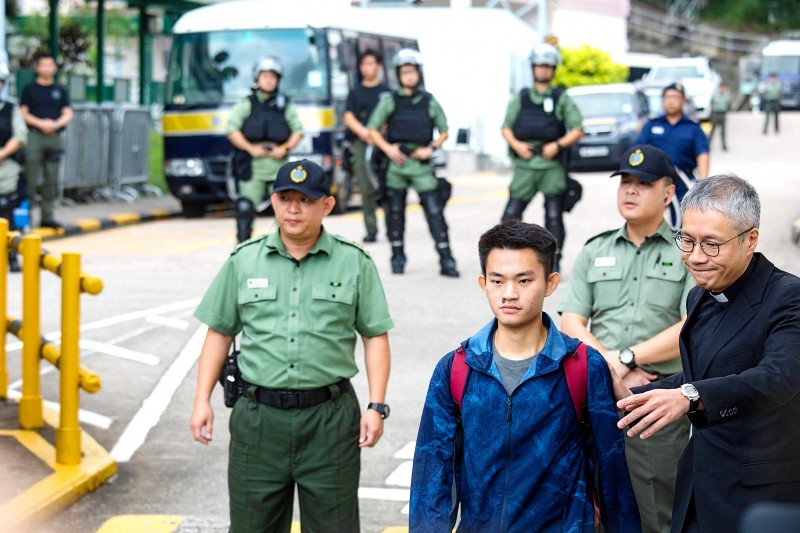 Murder suspect Chan Tong-kai, second left, accompanied by Anglican priest Peter Koon, right, leaves Pik Uk Prison in Hong Kong yesterday.  Photo: Bloomberg