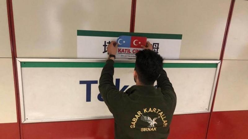 一名參與公民不服從運動的土耳其民眾,在中文站牌上覆蓋寫有「中國劊子手」字樣的圖示。(擷取自《寒冬》雜誌)