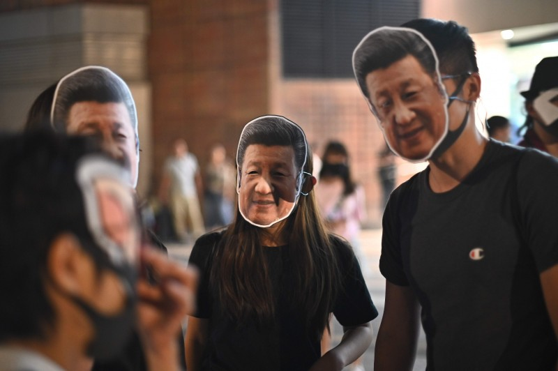 中共十九屆四中全會日期喬不定,被外界指是權鬥慘烈。圖為香港年輕人掛中共領導人習近平照片上街,以突圍禁蒙面法。(法新社)
