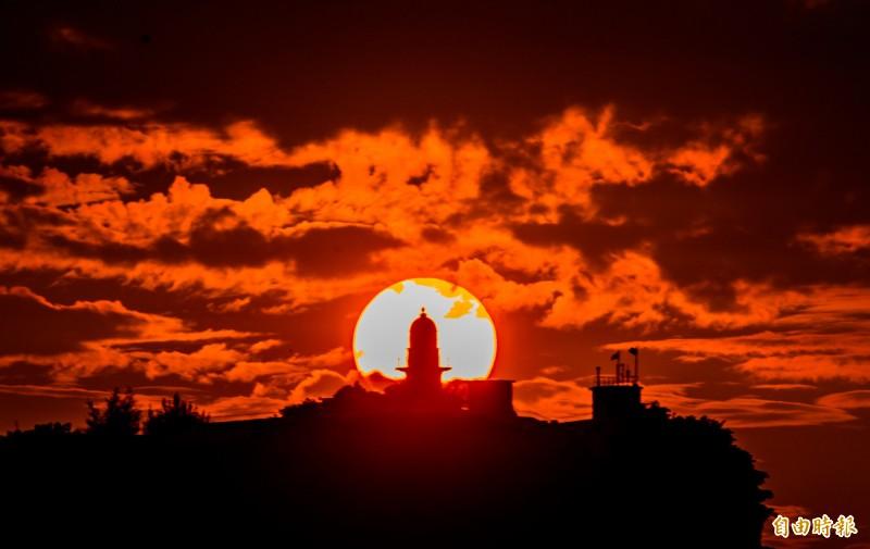 這幾天在高雄香蕉碼頭棧二庫欣賞夕陽落日,落日剛好就在高雄旗津燈塔正後方。(記者張忠義攝)